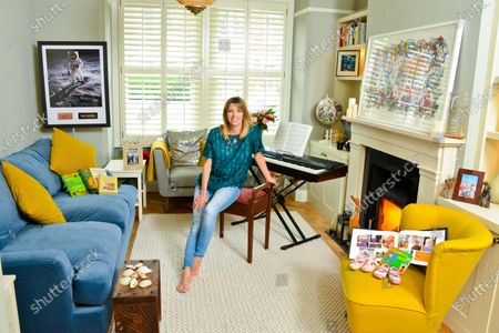 Stock Photo of Claire Goose 'My Haven'-Living Room of her West London Home 25.6.2019.  1.Childrens Book 'Goodnight Moon' 1st Shoes and Photo book 2.Royal TV Society Award 3. Piano 4. Wildlife Picture/Map of the World 5. Shells from Norfolk 6.Wedding Photo  7.Holly Aird from Waking The Dead bought me this Neckless for my 30th birthday 8.This photo is in my office-just reminds me of the fun we had on set 9.Buzz Aldrin signed Moon Photo  10.Books for love of cooking-my main thing is baking cakes and puddings. My gran was a great baker and so is my mum 11.CG in Africa Photo & native figures (elder brother, Duncan, an entrepreneur who started up the One Drinks company (best known for One Water), which donates its profit to clean water projects in Africa.