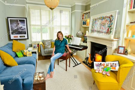Stock Image of Claire Goose 'My Haven'-Living Room of her West London Home 25.6.2019.  1.Childrens Book 'Goodnight Moon' 1st Shoes and Photo book 2.Royal TV Society Award 3. Piano 4. Wildlife Picture/Map of the World 5. Shells from Norfolk 6.Wedding Photo  7.Holly Aird from Waking The Dead bought me this Neckless for my 30th birthday 8.This photo is in my office-just reminds me of the fun we had on set 9.Buzz Aldrin signed Moon Photo  10.Books for love of cooking-my main thing is baking cakes and puddings. My gran was a great baker and so is my mum 11.CG in Africa Photo & native figures (elder brother, Duncan, an entrepreneur who started up the One Drinks company (best known for One Water), which donates its profit to clean water projects in Africa.