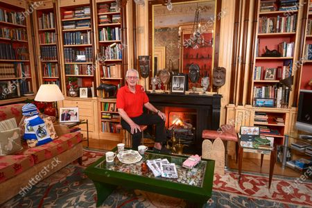 Robert Lacey 'My Haven' - Library of his London Home 17.1.2020 Bristol Rovers scarf and hat.  African masks on the mantlepiece. Ivory Coast tribal masks  Edward VIII and Queen Alexandra souvenir mugs and cups, Pink Thunderbird convertible Brass Bedouin coffee pots, from my spell living in Saudi Arabia to write The Kingdom.  Would like to mention my first wife Sandi  Yemeni catechism boards with a naughty rooster and cheeky pelican. Photograph of myself water-skiing - my main summer hobby Family photos + Sparkly green turtle made by my granddaughter, Ariella, daughter Scarlett is a producer, My elder son Sasha works for Nike, My younger son Bruno, founder of the gardening charity Urban Growth, Photos of Jane and myself. 45-minutes with Hamlet. Programme of the last production of Kent Opera Framed photograph of my wife, Jane, as one of the six Maids of Honour to the Queen at the 1953 Coronation (signed Elizabeth R).Photo of Mum Vida