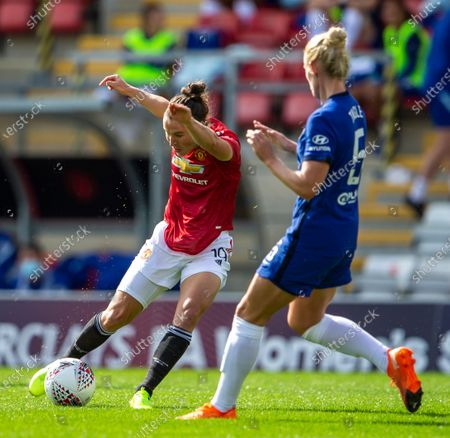 Jane Ross of Manchester United Women shoots the ball past Sophie Ingle of Chelsea Women; Leigh Sports Village, Lancashire, England; Women's English Super League, Manchester United Women versus Chelsea Women.