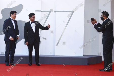 Producer Vivek Gomber, right, takes a photograph of director Chaitanya Tamhane, from left, and actor Aditya Modak upon arrival at the premiere of the film 'The Disciple' during the 77th edition of the Venice Film Festival in Venice, Italy