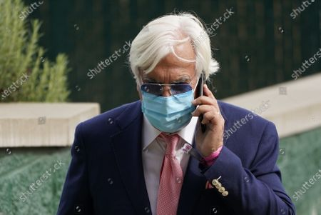 Trainer Bob Baffert makes a phone call following a race before the 146th running of the Kentucky Oaks at Churchill Downs, in Louisville, Ky