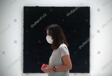 A visitor wearing a face masks seen walking past a painting during the exhibition 'Ergo Sum' at Contemporary Art Centre. Mexican artist, Bosco Sodi arrives with around 40 works such as black monochromatic paintings in different formats and gold sculptures. The artist is known for his use of raw, natural materials to create large-scale textured paintings and objects. The exhibition will run in Malaga from 04 September to 06 December 2020.