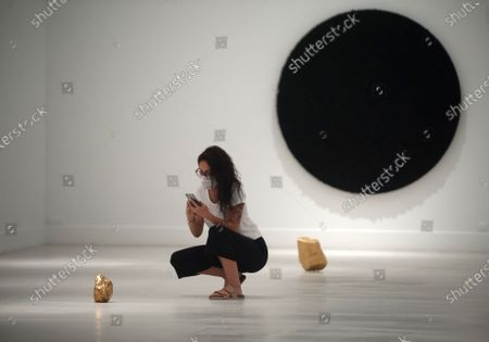 A visitor wearing a face mask taking a picture of a gold sculpture during the exhibition 'Ergo Sum' at Contemporary Art Centre.  Mexican artist, Bosco Sodi arrives with around 40 works such as black monochromatic paintings in different formats and gold sculptures. The artist is known for his use of raw, natural materials to create large-scale textured paintings and objects. The exhibition will run in Malaga from 04 September to 06 December 2020.