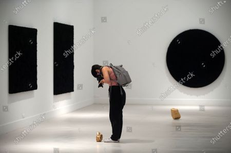 A photographer taking a picture of a gold sculpture during the exhibition 'Ergo Sum' at Contemporary Art Centre.  Mexican artist, Bosco Sodi arrives with around 40 works such as black monochromatic paintings in different formats and gold sculptures. The artist is known for his use of raw, natural materials to create large-scale textured paintings and objects. The exhibition will run in Malaga from 04 September to 06 December 2020.
