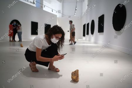 A visitor taking a picture of a gold sculpture during the exhibition 'Ergo Sum' at Contemporary Art Centre. Mexican artist, Bosco Sodi arrives with around 40 works such as black monochromatic paintings in different formats and gold sculptures. The artist is known for his use of raw, natural materials to create large-scale textured paintings and objects. The exhibition will run in Malaga from 04 September to 06 December 2020.