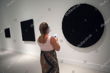 A visitor checking her mobile phone as she looks at a painting during the exhibition 'Ergo Sum' at Contemporary Art Centre. Mexican artist, Bosco Sodi arrives with around 40 works such as black monochromatic paintings in different formats and gold sculptures. The artist is known for his use of raw, natural materials to create large-scale textured paintings and objects. The exhibition will run in Malaga from 04 September to 06 December 2020.