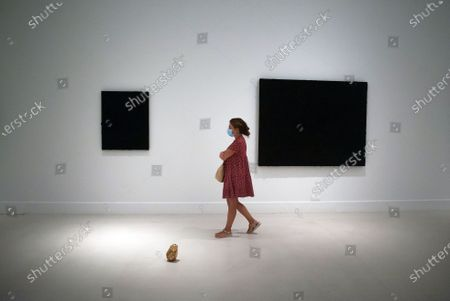 Stock Image of A visitor wearing a face masks walking past a painting during the exhibition 'Ergo Sum' at Contemporary Art Centre. Mexican artist, Bosco Sodi arrives with around 40 works such as black monochromatic paintings in different formats and gold sculptures. The artist is known for his use of raw, natural materials to create large-scale textured paintings and objects. The exhibition will run in Malaga from 04 September to 06 December 2020.