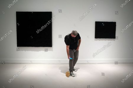Stock Photo of A visitor taking a picture of a gold sculpture during the exhibition 'Ergo Sum' at Contemporary Art Centre. Mexican artist, Bosco Sodi arrives with around 40 works such as black monochromatic paintings in different formats and gold sculptures. The artist is known for his use of raw, natural materials to create large-scale textured paintings and objects. The exhibition will run in Malaga from 04 September to 06 December 2020.