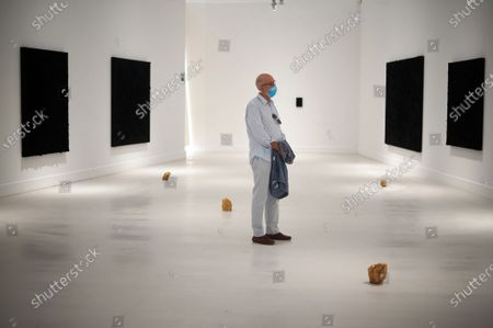 A visitor wearing a face mask looking at a painting during the exhibition 'Ergo Sum' at Contemporary Art Centre. Mexican artist, Bosco Sodi arrives with around 40 works such as black monochromatic paintings in different formats and gold sculptures. The artist is known for his use of raw, natural materials to create large-scale textured paintings and objects. The exhibition will run in Malaga from 04 September to 06 December 2020.