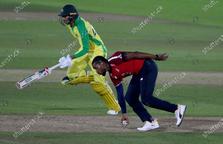 England's Chris Jordan, right, picks the ball to run-out Australia's Ashton Agar, left, during the first Twenty20 cricket match between England and Australia, at the Ageas Bowl in Southampton, England