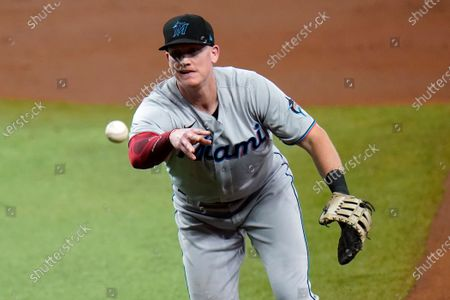Miami Marlins first baseman Garrett Cooper flips the ball to pitcher Pablo Lopez in time to get Tampa Bay Rays' Manuel Margot at first base on a ground out during the second inning of a baseball game, in St. Petersburg, Fla