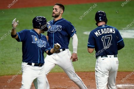 Tampa Bay Rays' Kevin Kiermaier, center, scores with Yoshitomo Tsutsugo, of Japan, left, and Austin Meadows, right, on a three-run double by Michael Perez off Miami Marlins starting pitcher Pablo Lopez during the fourth inning of a baseball game, in St. Petersburg, Fla