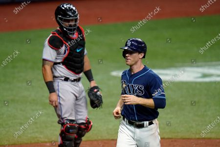 Tampa Bay Rays' Joey Wendle, right, scores in front of Miami Marlins catcher Jorge Alfaro on a bases loaded walk by starting pitcher Pablo Lopez to Kevin Kiermaier during the fourth inning of a baseball game, in St. Petersburg, Fla