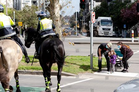 A young girl acknowledges the police officers on horseback during the Anti-Lockdown Protest on September 05, 2020 in Melbourne, Australia. Stage 4 restrictions are in place from 6pm on Sunday 2 August for metropolitan Melbourne. This includes a curfew from 8pm to 5am every evening. During this time people are only allowed to leave their house for work, and essential health, care or safety reasons.
