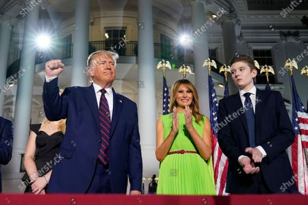 """Stock Image of President Donald Trump, first lady Melania Trump and Barron Trump stand on the South Lawn of the White House on the fourth day of the Republican National Convention, in Washington. It's called a """"permission structure."""" President Donald Trump's campaign is trying to construct an emotional and psychological gateway to help disenchanted voters feel comfortable voting for the president again despite their reservations about him personally"""