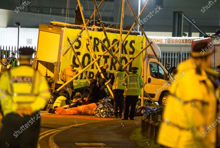 London, UK. Members of the Extinction Rebellion (XR) environmental campaign group maintain the blockade Broxbourne in Hertfordshire throughout the night using vehicles and bamboo lock-ons to try to prevent the Sun, Times, Telegraph and Mail newspapers from reaching newsstands on Saturday. XR plan to disrupt areas of central London with actions planned over the next two weeks, until MP's back the Climate and Ecological Emergency Bill and prepare for crisis with a National Citizens' Assembly.