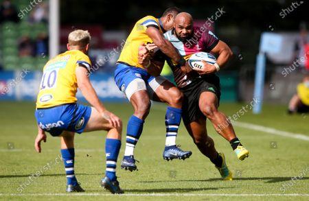 Paul Lasike of Harlequins breaks and is tackled by Semesa Rokoduguni of Bath - Rhys Priestland of Bath (L)