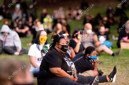 Stock Picture of Shawn Roberts, center, listens to a speech during the 100th consecutive day of demonstrations in Portland, Ore., on . The demonstrations began over the killing of George Floyd