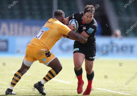 Brad Barritt of Saracens is tackled by Simon McIntyre of Wasps