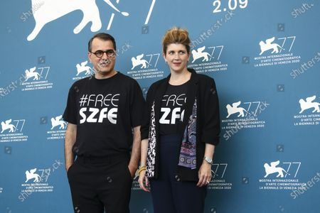 """Director Kornel Mundruczo, left, and writer Kata Weber pose for photographers at the photo call for the film 'Pieces of A Woman' during the 77th edition of the Venice Film Festival in Venice, Italy, . They are wearing t-shirts with the message """"Free SZFE,"""" a reference to a campaign protesting management changes at the University of Theatre and Film Arts (known by its acronym SZFE) imposed by the Victor Orban government that critics say will undermine the university's autonomy"""