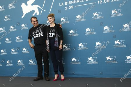 """Stock Photo of Director Kornel Mundruczo, left, and writer Kata Weber pose for photographers at the photo call for the film 'Pieces of A Woman' during the 77th edition of the Venice Film Festival in Venice, Italy, . They are wearing t-shirts with the message """"Free SZFE,"""" a reference to a campaign protesting management changes at the University of Theatre and Film Arts (known by its acronym SZFE) imposed by the Victor Orban government that critics say will undermine the university's autonomy"""