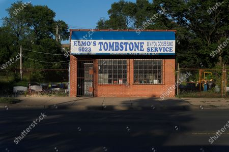 """The afternoon sun casts shadows across State Street in front of Elmo's Tombstone Service on the Chicago's Southside. The slogan """"Be 4 You Go, See Elmo"""" was coined by original Elmo's Tombstone Service owner, Robert Williams, graces the awning of the small shop now owned by Hosea Knox"""