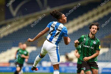 Stock Image of Huddersfield Town Defender Romoney Crichlow-Noble (27 heads the ball at goal during the EFL Cup match between Rochdale and Huddersfield Town at the John Smiths Stadium, Huddersfield
