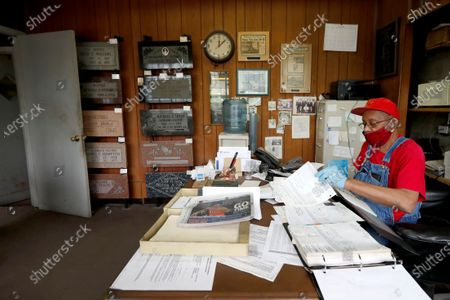 Stock Photo of Hose Knox, owner of Elmo's Tombstone Service tackles the backlog of paperwork, in his office surrounded by tombstone design samples and decades old memorabilia on Chicago's Southside. Knox and his wife, Bobbie, bought the business from Robert Williams in 1987. She died of cancer in 2012, but the 81-year-old Knox continues making tombstones on the city's predominantly Black South Side, and Bobbie remains listed on his business cards