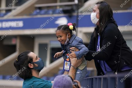 Stock Picture of Three-year-old Alexis Olympia Ohanian Jr., center, daughter of Serena Williams, of the United States, is handed down to courtside after watching her mother play against Sloane Stephens, of the United States, during the third round of the US Open tennis championships, in New York
