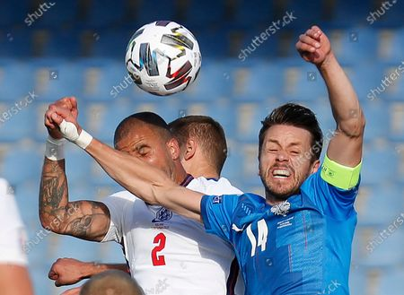 England's Kyle Walker, left, is challenged by Iceland's Kari Arnason during the UEFA Nations League soccer match between Iceland and England in Reykjavik, Iceland