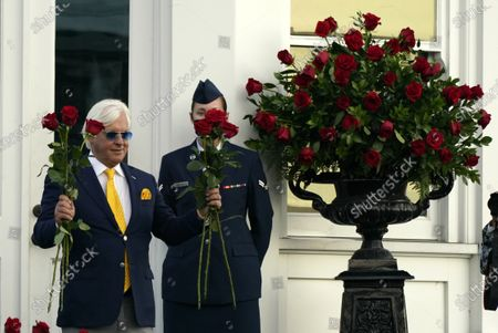 Trainer Bob Baffert holds roses after John Velazquez rode Authentic to victory in the 146th running of the Kentucky Derby at Churchill Downs, in Louisville, Ky