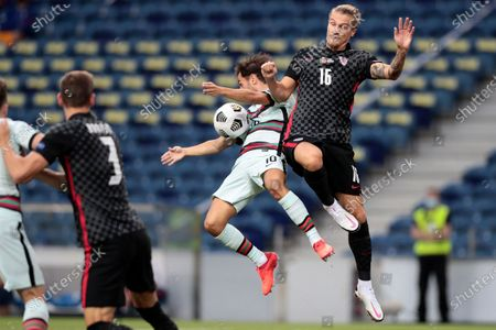 Portugal's Bernardo Silva jumps for the ball with Croatia's Tin Jedvaj, right, during the UEFA Nations League soccer match between Portugal and Croatia at the Dragao stadium in Porto, Portugal