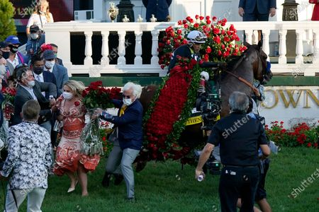Trainer Bob Baffert is knocked out of the way as Jockey John Velazquez try to control Authentic in the winners' circle after winning the 146th running of the Kentucky Derby at Churchill Downs, in Louisville, Ky