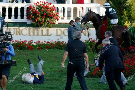 Trainer Bob Baffert is knocked to the ground as Jockey John Velazquez attempts to control Authentic in the winners' circle after winning the 146th running of the Kentucky Derby at Churchill Downs, in Louisville, Ky