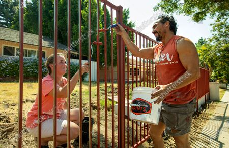 Melinda Mena and her husband Rick apply primer to a rod iron fence in front of their home on Reseda Blvd. in Porter Ranch, before painting it a dark bronze. (Mel Melcon / Los Angeles Times)