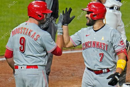 Cincinnati Reds' Eugenio Suarez (7) celebrates with Mike Moustakas after hitting a solo home run, his third homer of the game, off Pittsburgh Pirates relief pitcher Derek Holland in the eighth inning of a baseball game in Pittsburgh