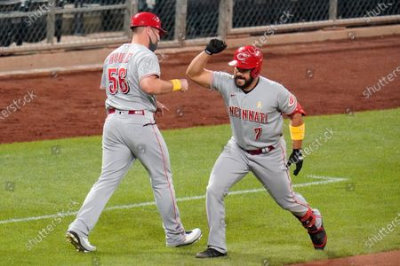 Cincinnati Reds' Eugenio Suarez (7) celebrates with third base coach J.R. House after hitting a solo home run, his third homer of the game, off Pittsburgh Pirates relief pitcher Derek Holland in the eighth inning of a baseball game in Pittsburgh