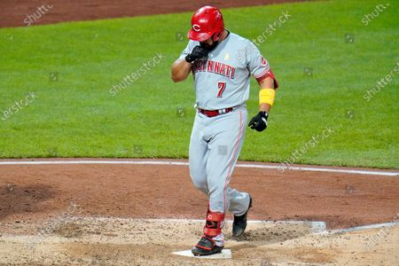 Cincinnati Reds' Eugenio Suarez steps on home plate after hitting a solo home run, his third homer of the game, off Pittsburgh Pirates relief pitcher Derek Holland in the eighth inning of a baseball game in Pittsburgh, . The Reds won 6-2