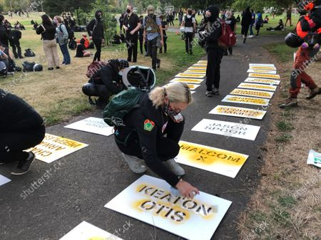 Protester Chelsea Jordan spray paints the names of slain Black men at a city park as protesters gathered for the 100th straight day against racism and police brutality, Saturday, Sept.5, 2020 in Portland, Ore