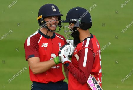 England's Jos Buttler, left, celebrates with batting partner Moeen Ali after their win in the second Twenty20 cricket match between England and Australia, at the Ageas Bowl in Southampton, England