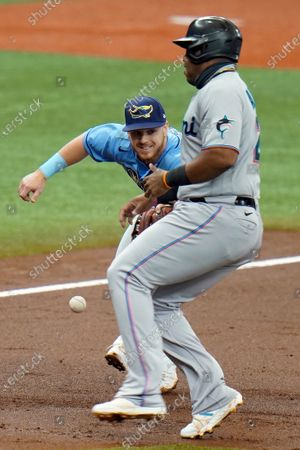 Miami Marlins' Jesus Aguilar steals third base as Tampa Bay Rays' Michael Brosseau, left, can't hang onto the throw from catcher Kevan Smith during the third inning of a baseball game, in St. Petersburg, Fla