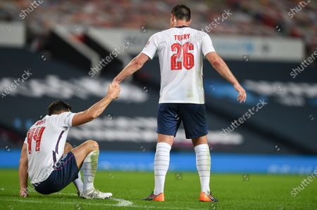John Terry helps Mark Wright to his fit at the end of the match which they lost on penalties in Soccer Aid for Unicef 2020 at Old Trafford, Manchester