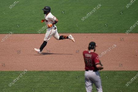 San Francisco Giants' Chadwick Tromp, top, rounds the bases after hitting a solo home run off of Arizona Diamondbacks pitcher Alex Young, bottom, during the third inning of a baseball game in San Francisco