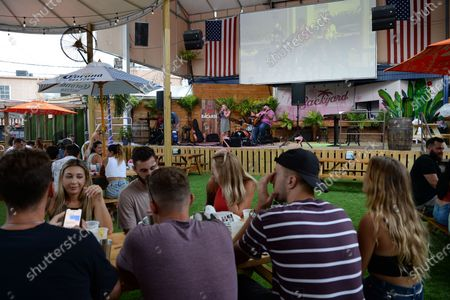 Stock Image of People look on as Bonn E Maiy performs at Backyard as it opens in Ft Lauderdale bringing live music back to South FL with an extensive menu and handcrafted cocktails all in an open air and covid safe environment