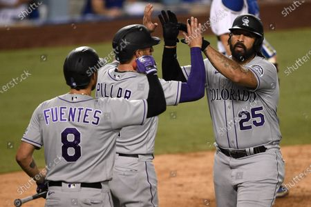 Colorado Rockies designated hitter Matt Kemp, from right to left, celebrates with Kevin Pillar and Josh Fuentes after a two-run home run during the eighth inning of a baseball game against the Los Angeles Dodgers in Los Angeles