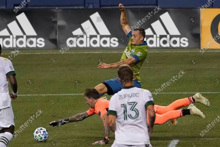 Seattle Sounders forward Jordan Morris, center, tangles with Portland Timbers goalkeeper Steve Clark as Timbers' Dario Zuparic (13) looks on during the first half of an MLS soccer match, in Seattle