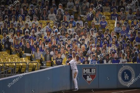 Los Angeles Dodgers left fielder A.J. Pollock looks past the left field wall after a foul ball hit by Colorado Rockies' Matt Kemp during the ninth inning of a baseball game in Los Angeles, . The Rockies won 7-6