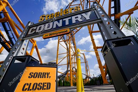 """In this photo made, a closed sign marks the blocked entrance to the """"Steelers Country"""" section, the home of the """"Steel Curtain"""" roller coaster, at Kennywood Park in West Mifflin, Pa. Visitors have been slow to return to U.S. theme parks that saw their seasons interrupted by the coronavirus crisis, causing some parks to reduce their operating days, slash ticket prices and close early for the year"""