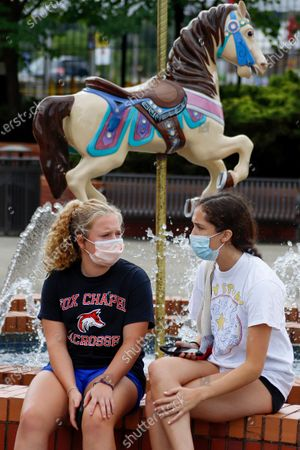 In this photo made, two youngsters wear required protective masks while sitting on the edge of a fountain with a carousel horse at Kennywood Park in West Mifflin, Pa. Visitors have been slow to return to U.S. theme parks that saw their seasons interrupted by the coronavirus crisis, causing some parks to reduce their operating days, slash ticket prices and close early for the year